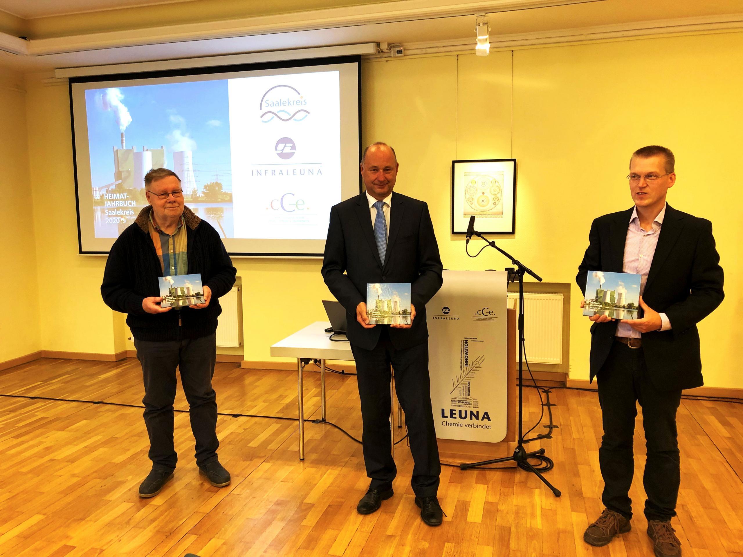 Drei Herren, in der Mitte Landrat Hartmut Handschak, halten das Jahrbuch in den Händen und schauen in die Kamera. ©Landkreis Saalekreis