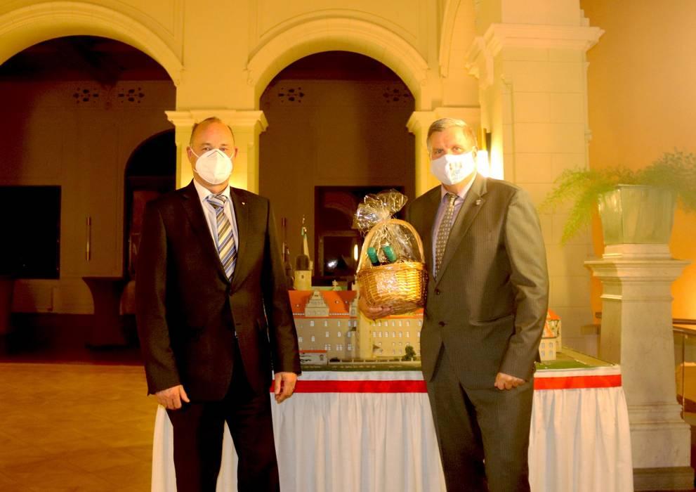 Landrat Hartmut Handschak steht links neben Lothar Rieser. Dieser hat einen Präsentkorb in der Hand. ©Susanne Lange