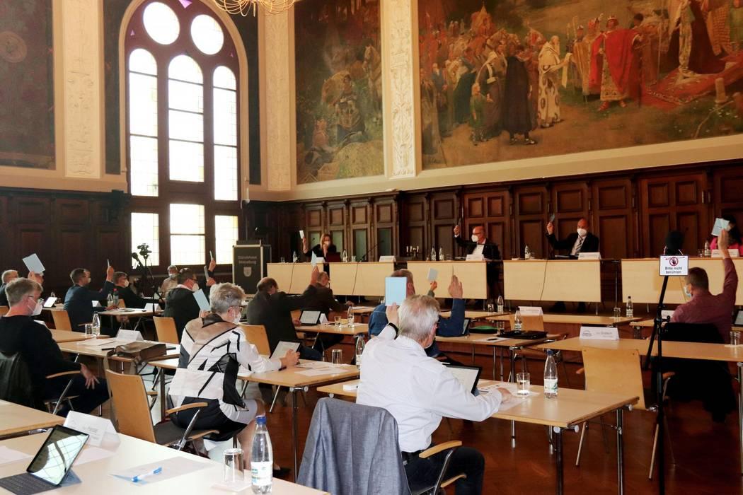 An Tischreihen in einem großen Saal sitzen Männer und Frauen. Sie heben einen Stimmzettel hoch. ©Landkreis Saalekreis