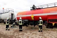 5 Feuerwehrmänner üben an einem Waggon, Leckagen zu schließen.